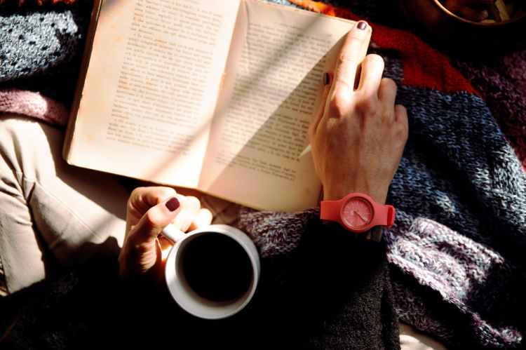 person reading book and holding coffee