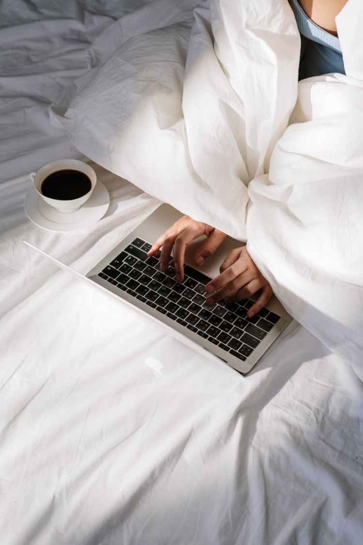 hands coffee laptop bed